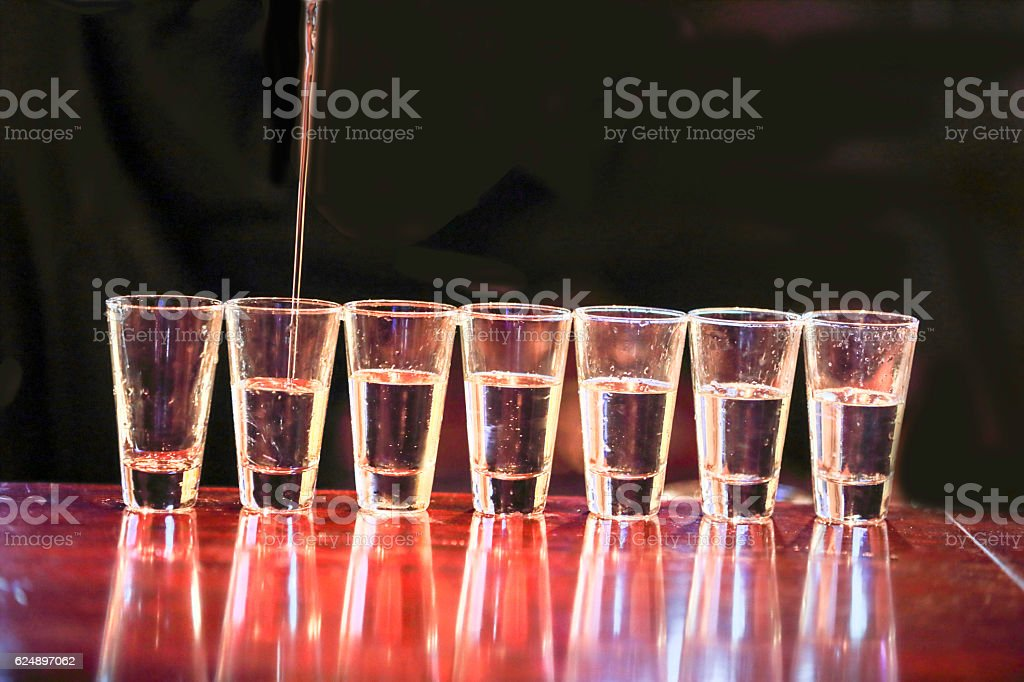 Series:Shots of tequila  are being poured on a bar stock photo