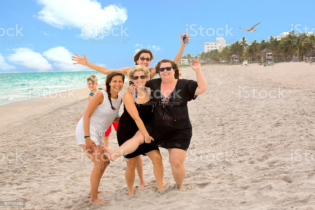 Series:Three women with diverse body shapes having fun at beach stock photo