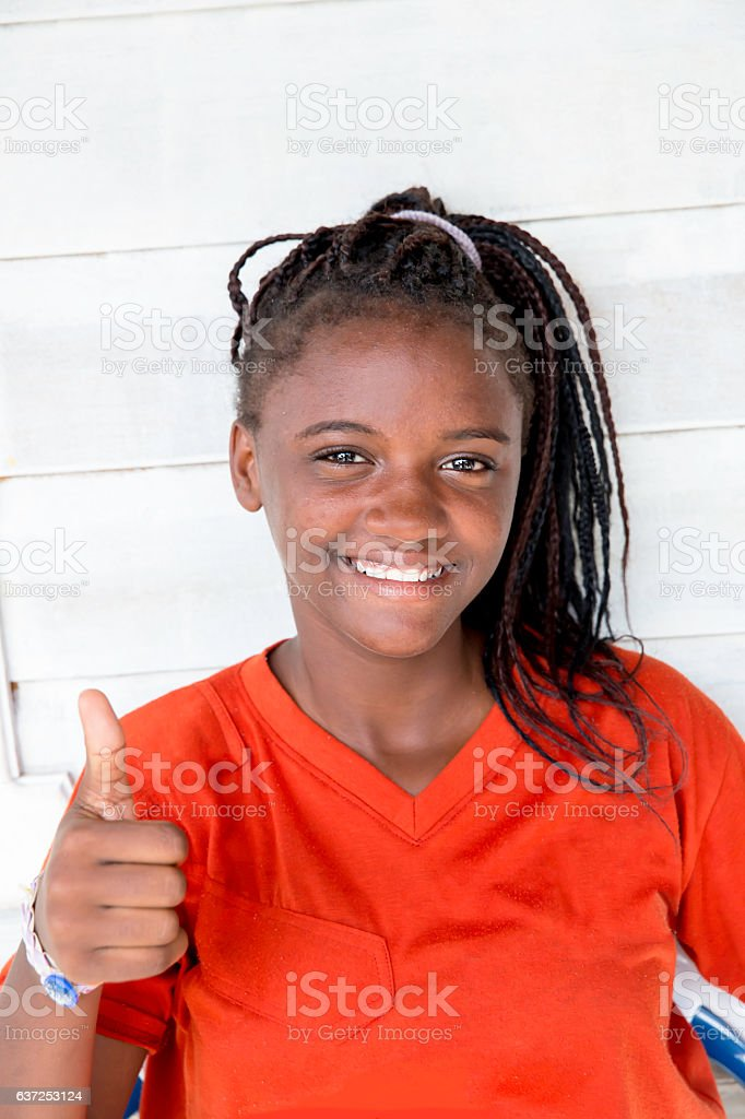 Series:Thumbs up from teenage Honduran girl with long braided hair stock photo