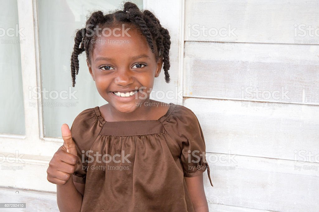 Series:Thumbs up! Young Honduran girl with braided hair stock photo