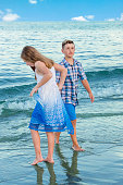 Series:Young caucasian brother and sister together on beach by water.