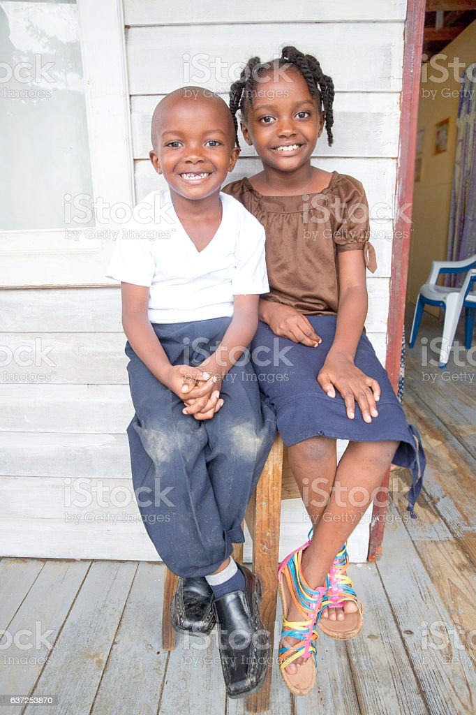 Series:Young Honduran brother and sister sitting on  front porch stock photo