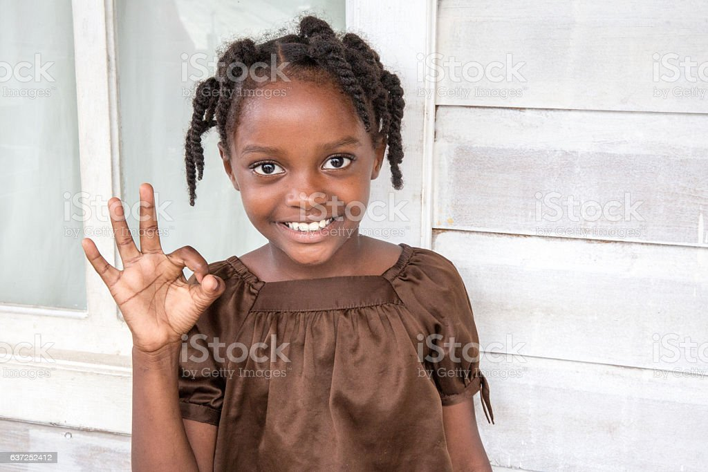 Series:Young Honduran girl with braided hair makes ok sign stock photo