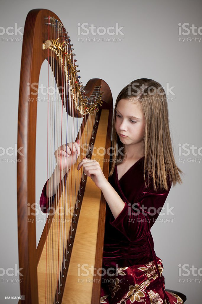 Serious 12-year old girl playing a harp stock photo