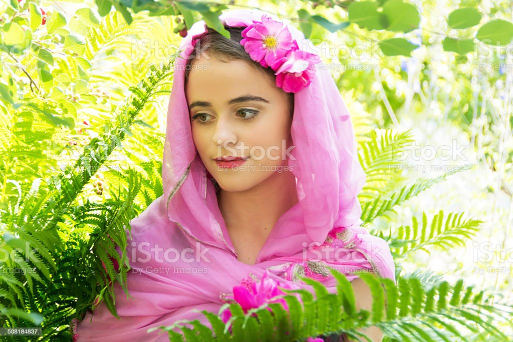Serious 15 year old in pink scarf, in bright garden stock photo