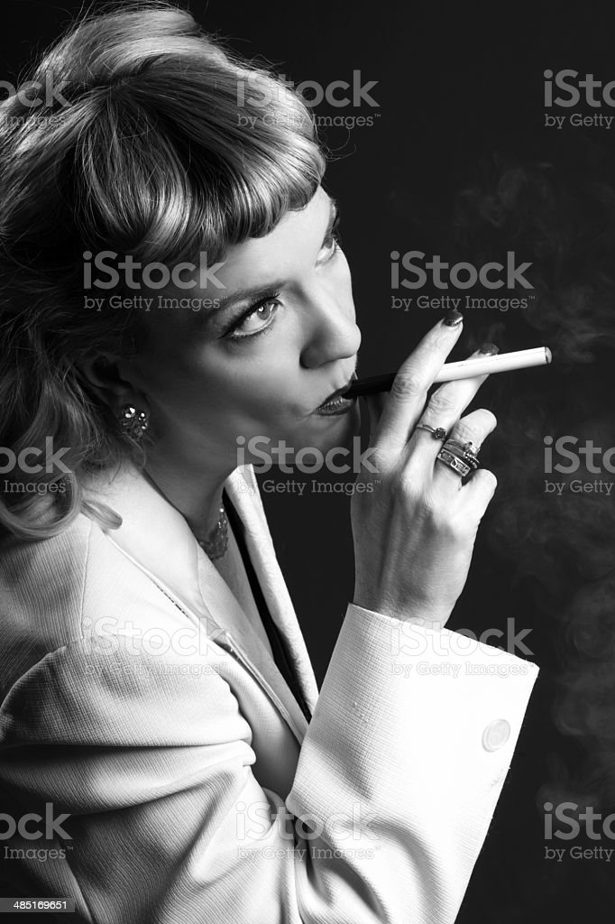 Serious 1940s styled woman puffing on e-cigarette. royalty-free stock photo