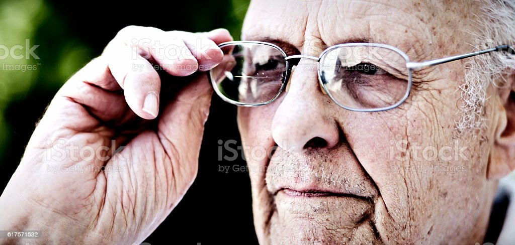 Serious 90 year old man looking through his spectacles stock photo