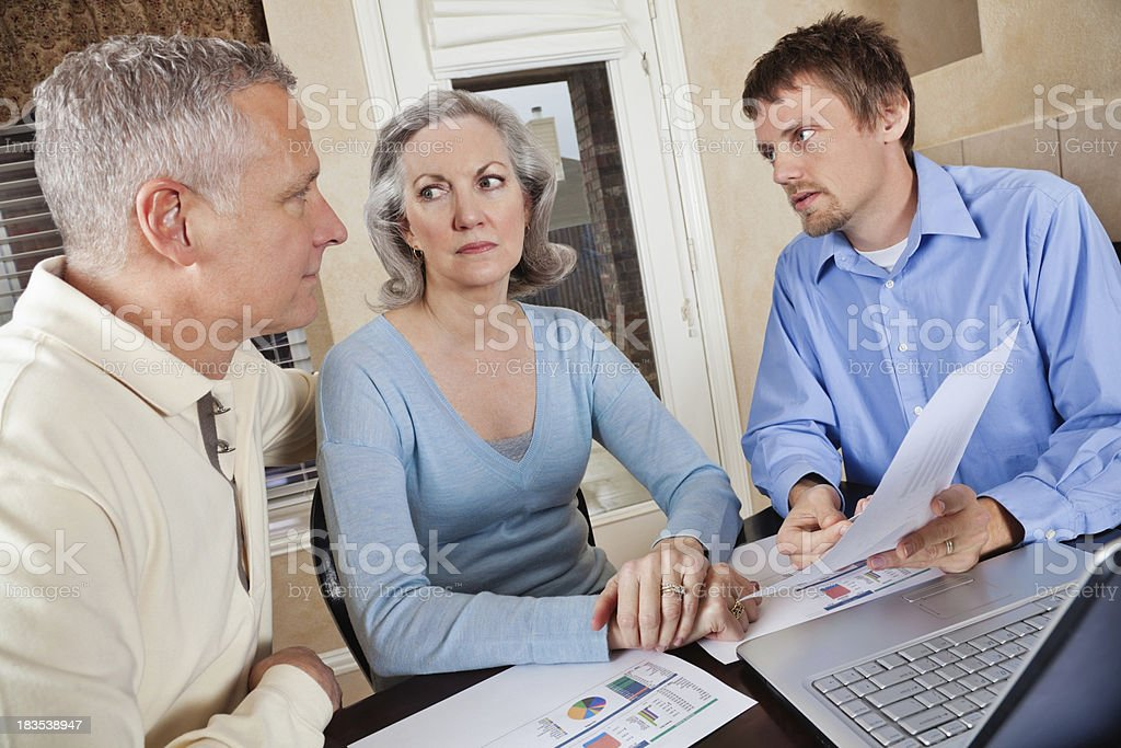 Serious Adult Couple in Meeting With Financial Advisor royalty-free stock photo