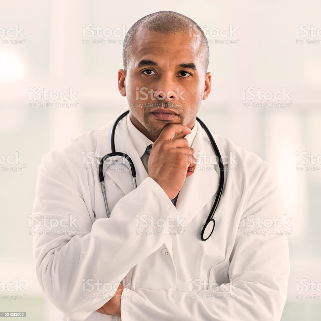 Serious African American doctor holding hand on chin at thinking. stock photo