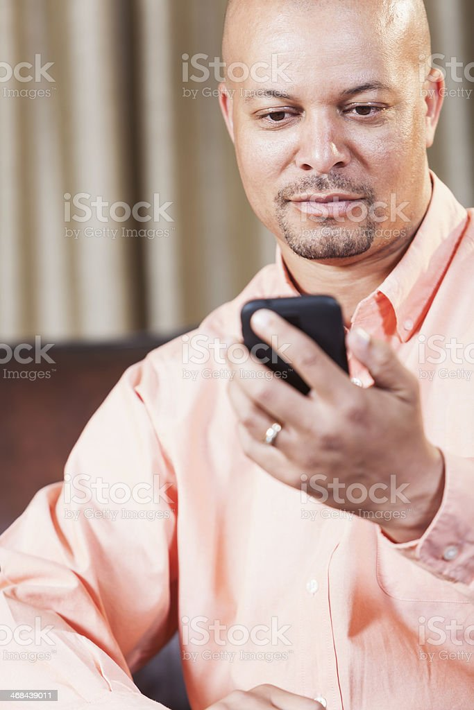 Serious African American man texting stock photo