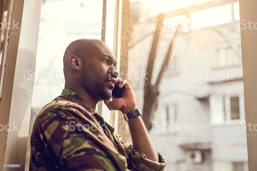 Serious African American soldier talking on the phone. stock photo