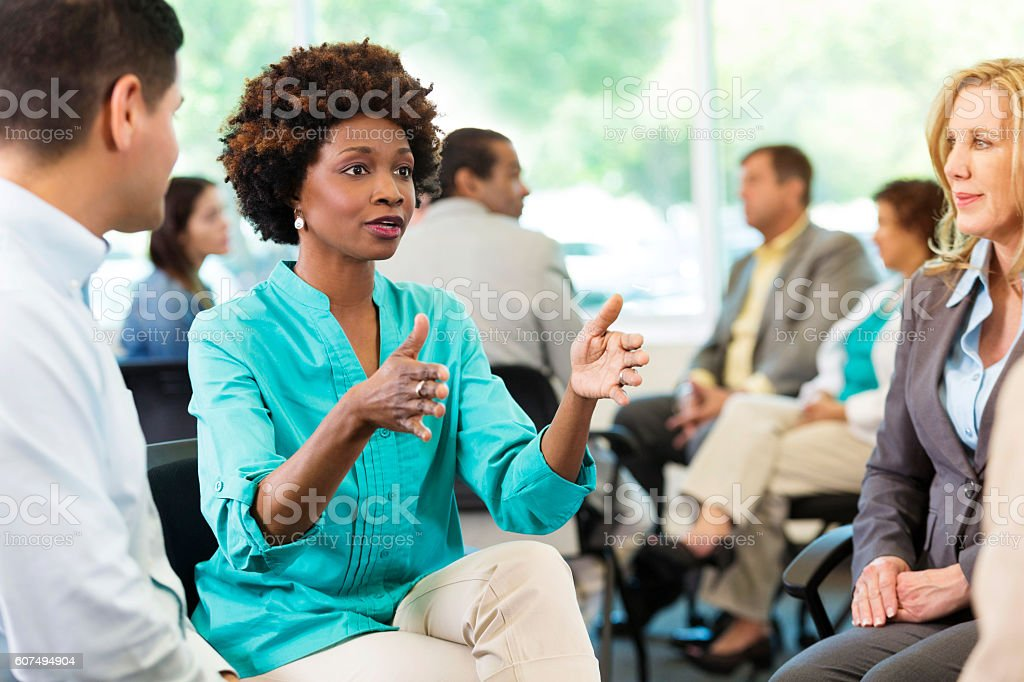 Serious African American woman makes a point during meeting stock photo