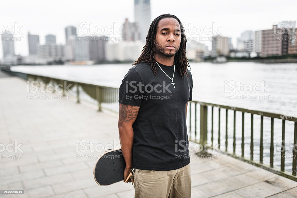 serious african man portrait with his skate stock photo