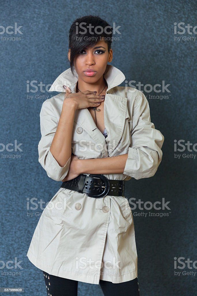 Serious African woman standing on grey background stock photo