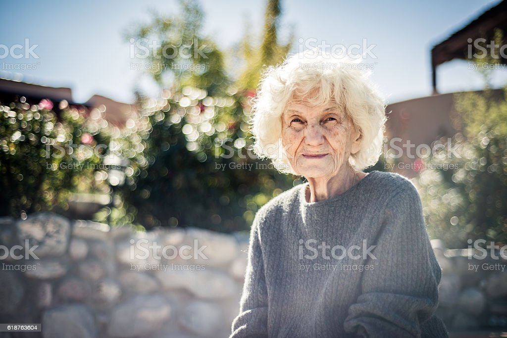 Serious and lonely senior woman outdoors stock photo