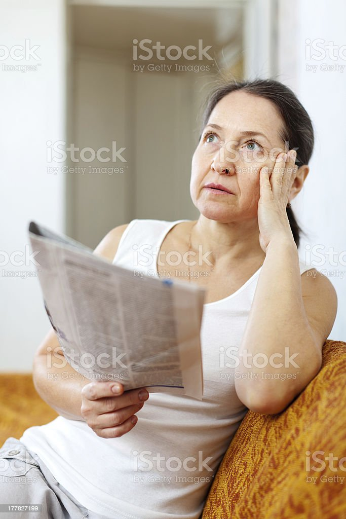 serious and wistful  woman with newspaper royalty-free stock photo