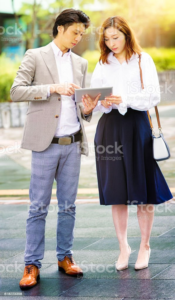 Serious Asian business people reading report on tablet stock photo