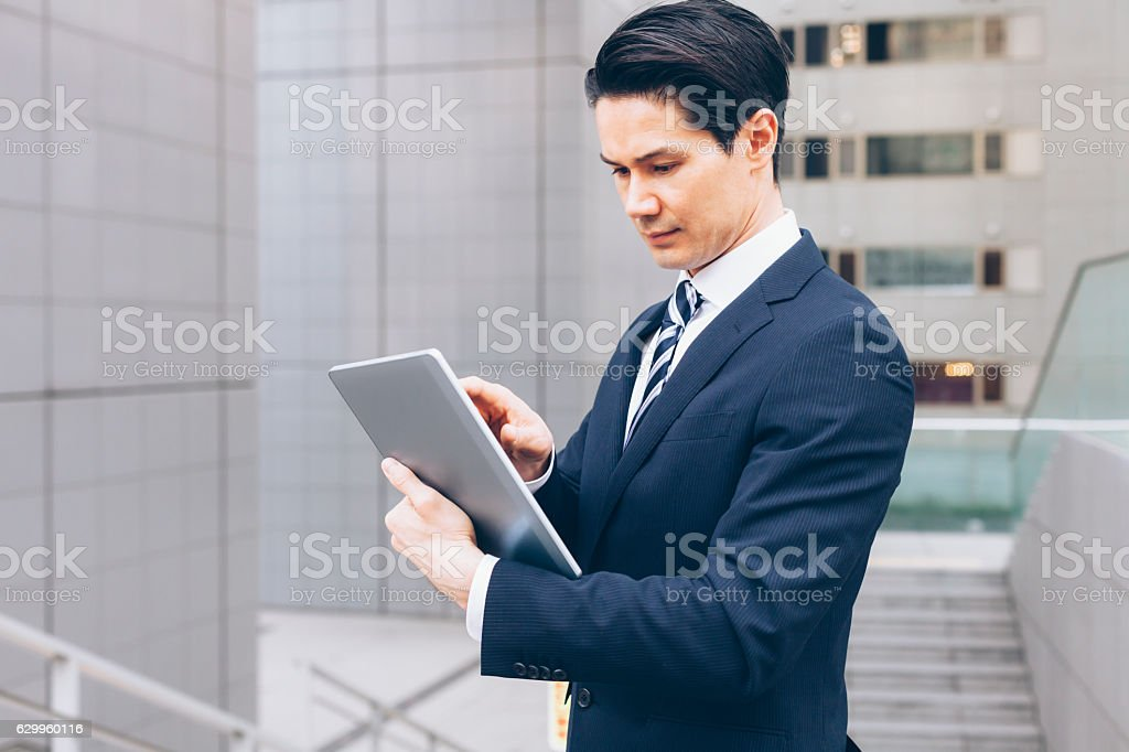 Serious asian businessman using digital tablet on street stock photo