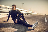 Serious athletic man stretching on a road.