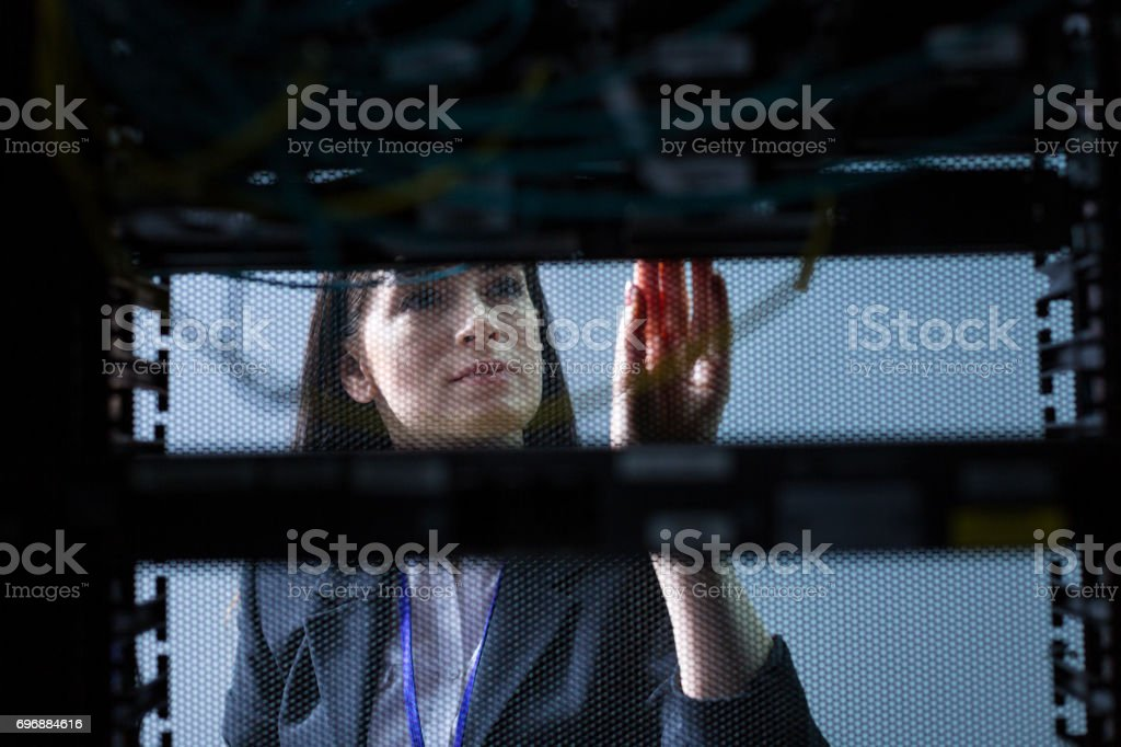 Serious attractive woman looking at the data server stock photo