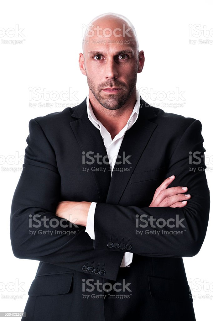 serious bald businessman with arms crossed stock photo