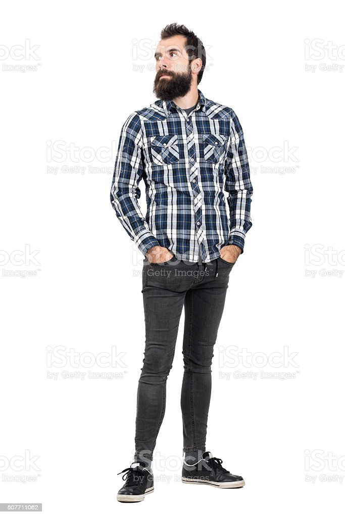Serious bearded hipster in plaid shirt looking away stock photo