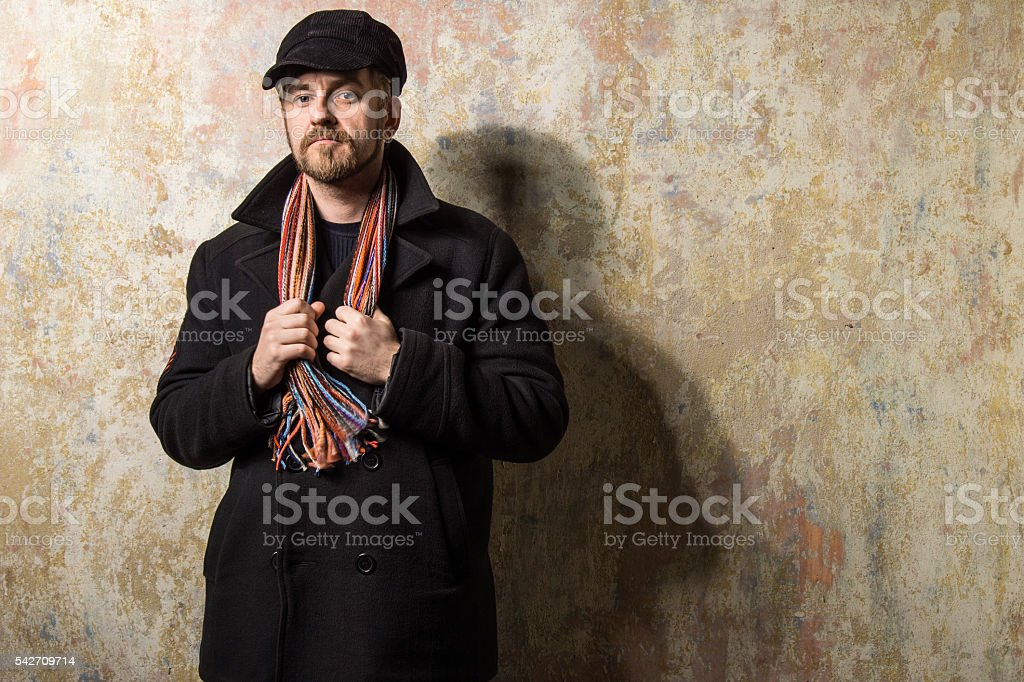 Serious bearded man wearing a cap and autumn coat stock photo