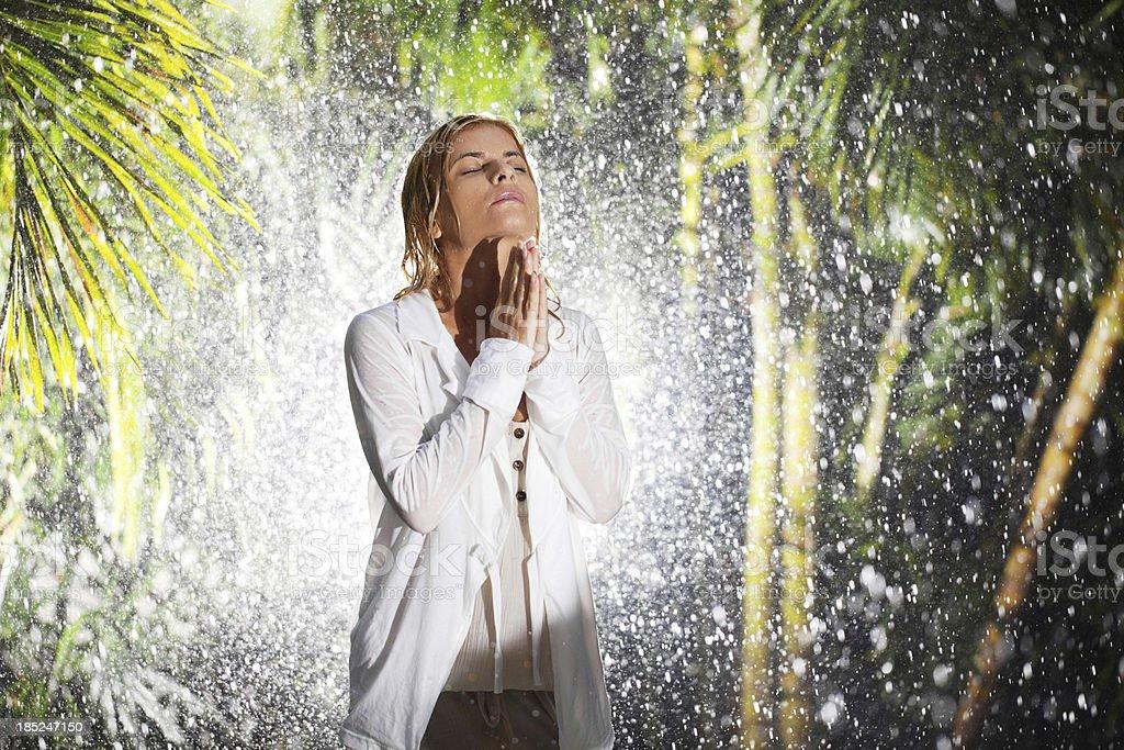 Serious blonde woman praying during tropical rain. royalty-free stock photo