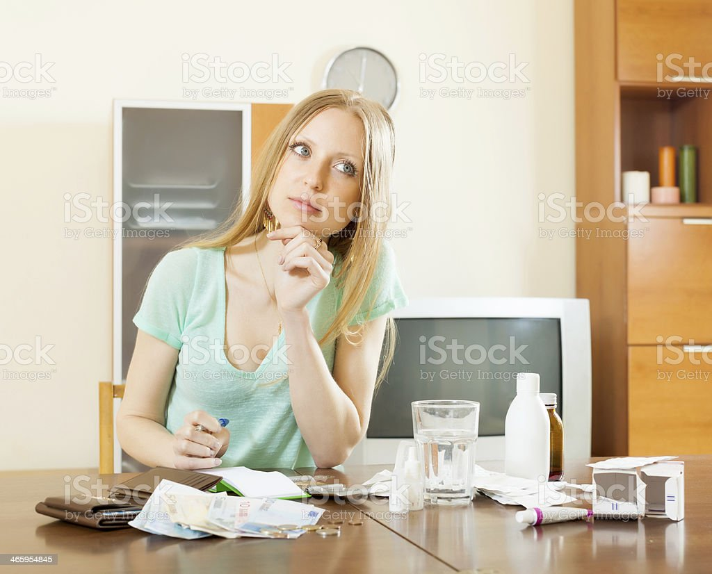 serious  blonde woman with medications and money stock photo