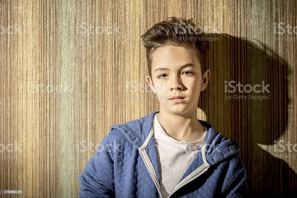 Serious boy leaning against a wall royalty-free stock photo