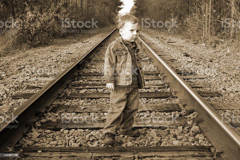 Serious Boy on Rail Road Tracks royalty-free stock photo