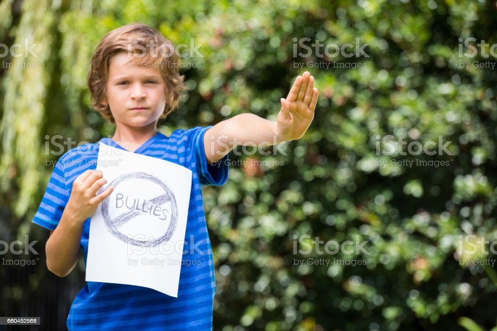 Serious boy saying stop with his hand and holding a message stock photo