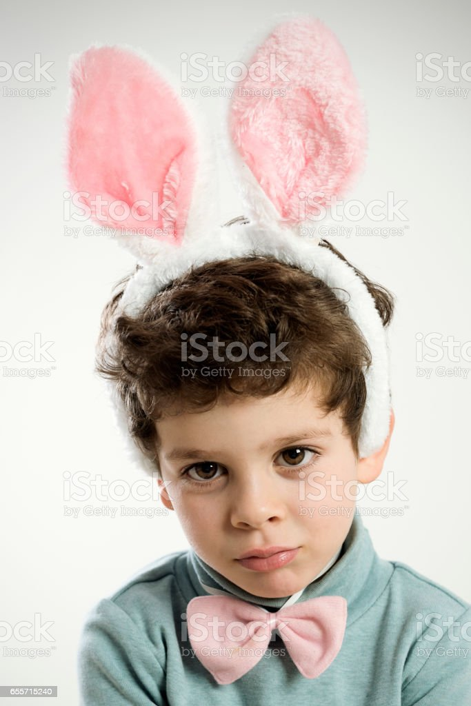 serious boy with rabbit ears stock photo