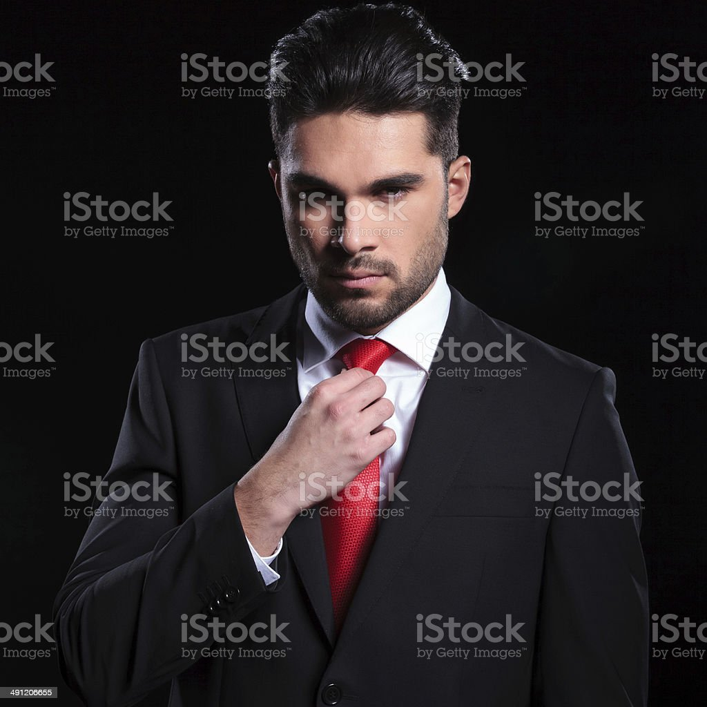 serious business man adjusts his tie royalty-free stock photo