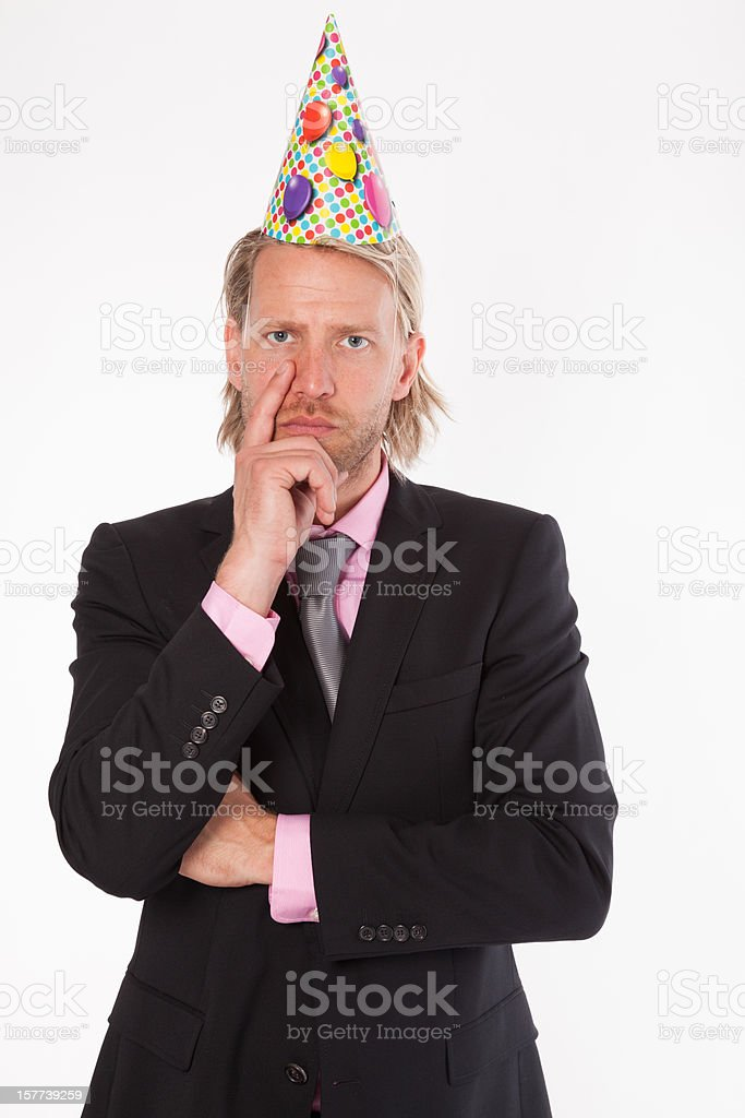 Serious business man with silly party hat stock photo