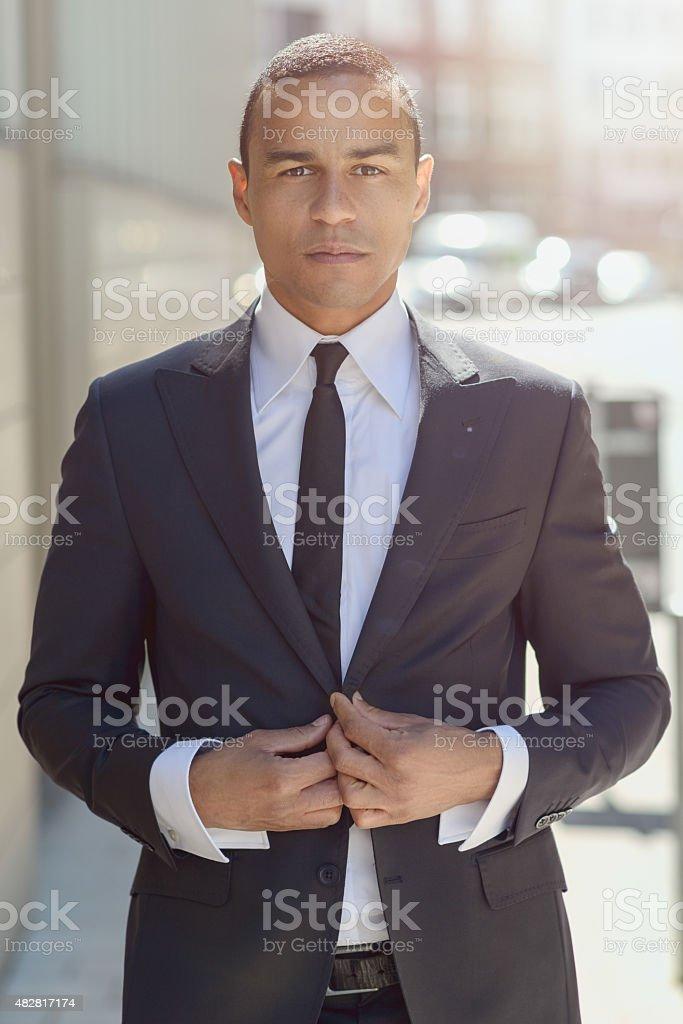 Serious businessman adjusting his jacket stock photo