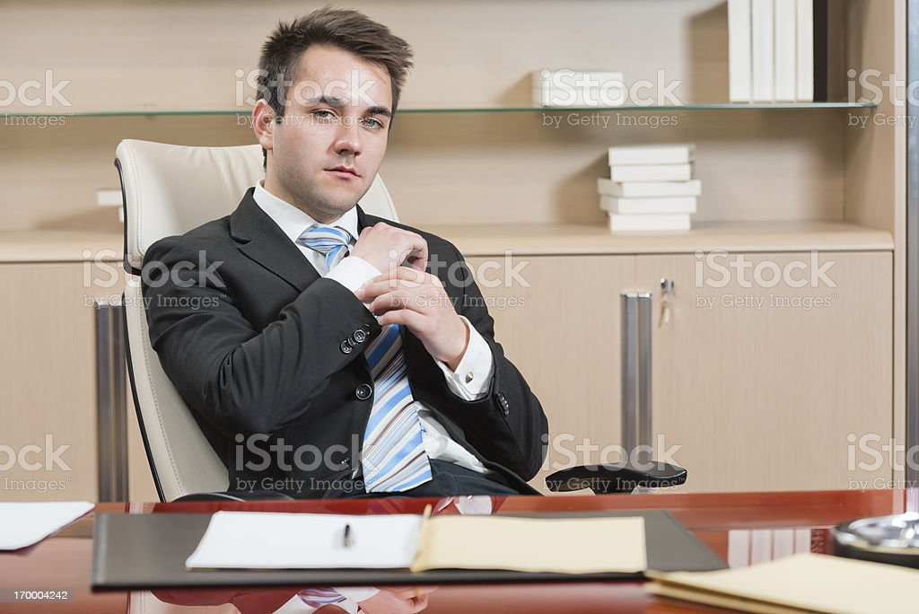 Serious businessman at office desk with a project folder royalty-free stock photo