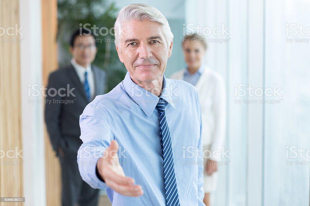 Serious businessman extending hand for handshake stock photo