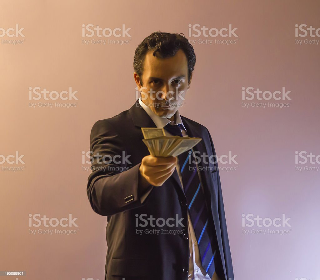 Serious Businessman Offering Dollars stock photo