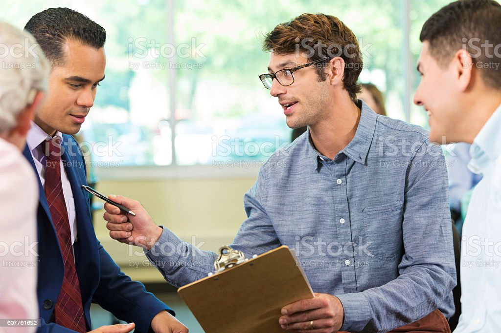Serious businessman points to a colleague stock photo