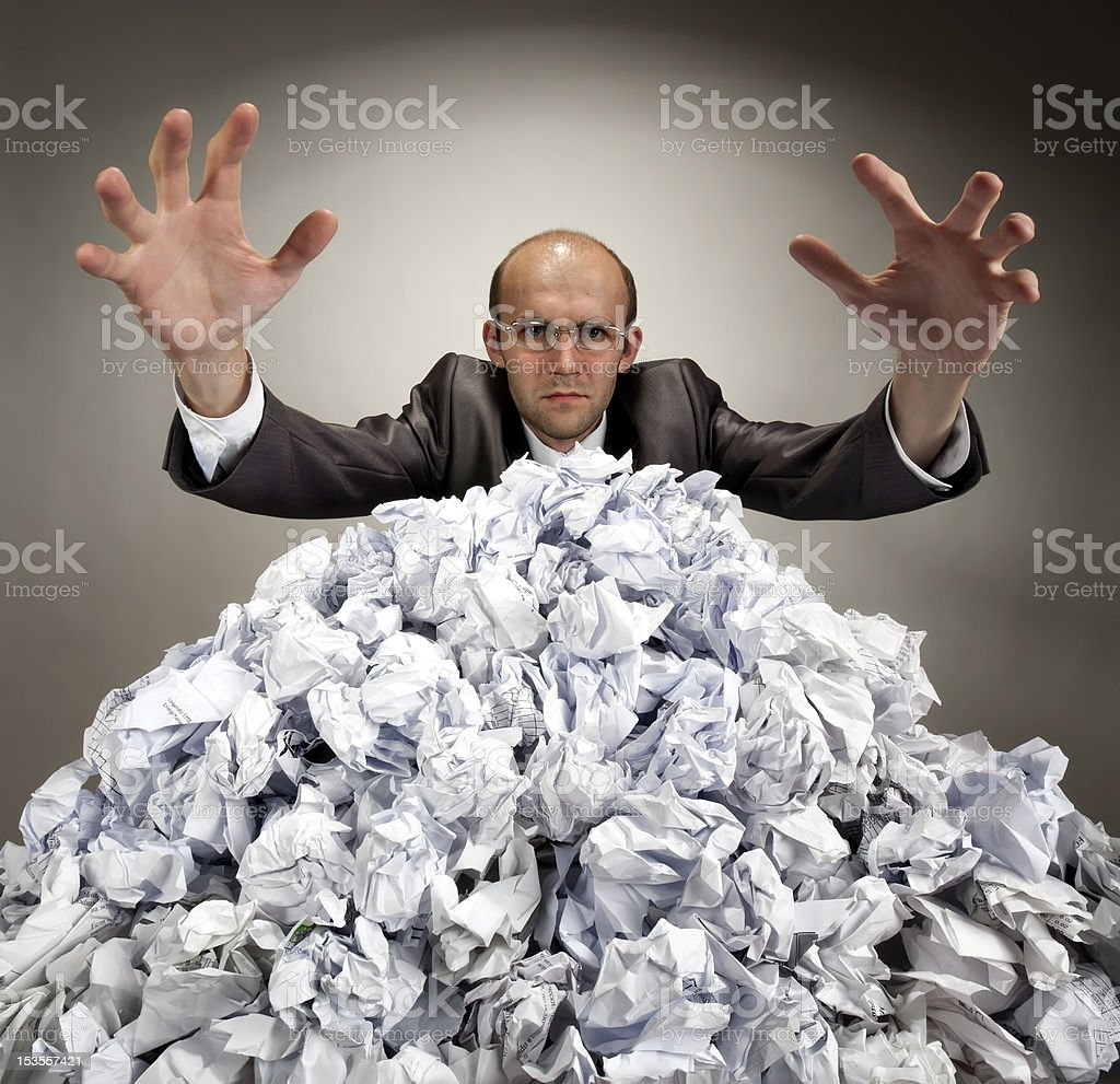 Serious businessman reaches out from crumpled papers royalty-free stock photo