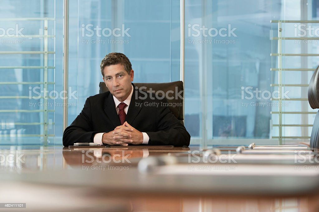 Serious businessman siting at conference table in office stock photo