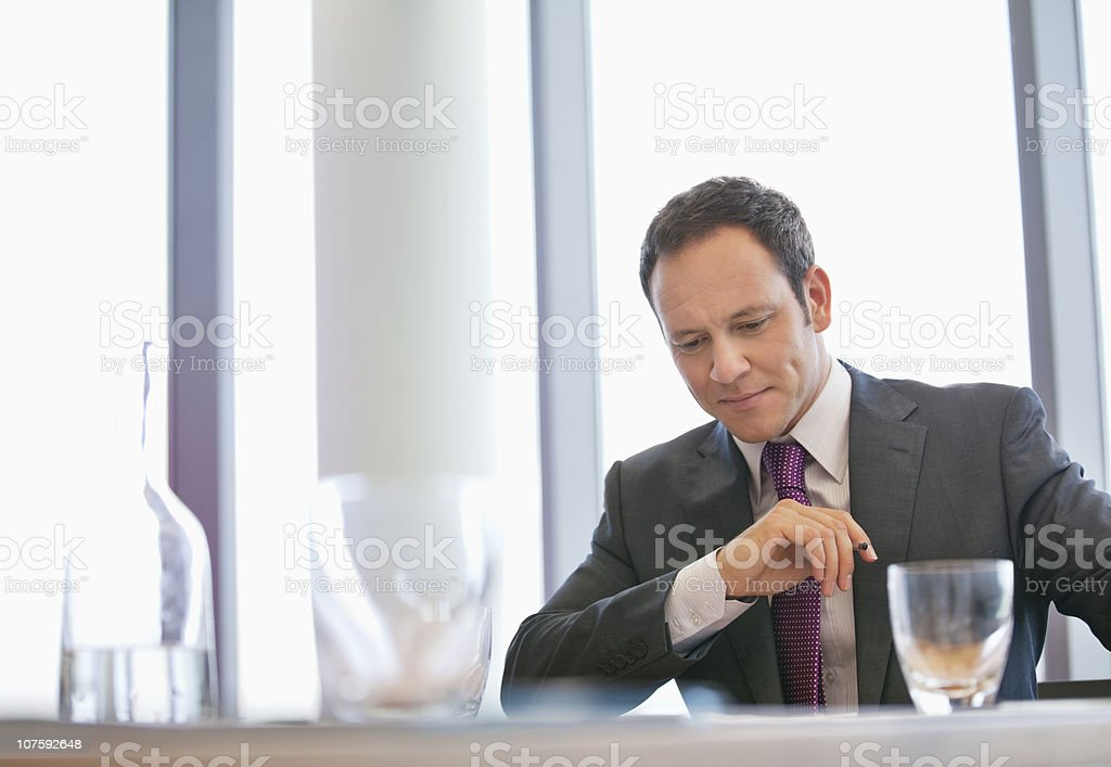 Serious businessman sitting at conference table in board room royalty-free stock photo