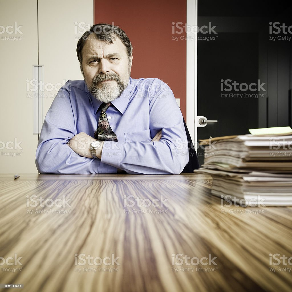 Serious Businessman Sitting at Desk with Papers stock photo