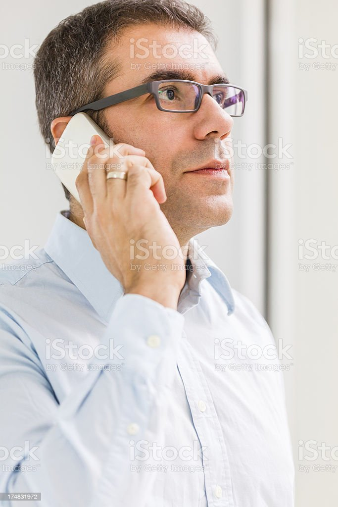 Serious businessman talking on a mobile phone royalty-free stock photo
