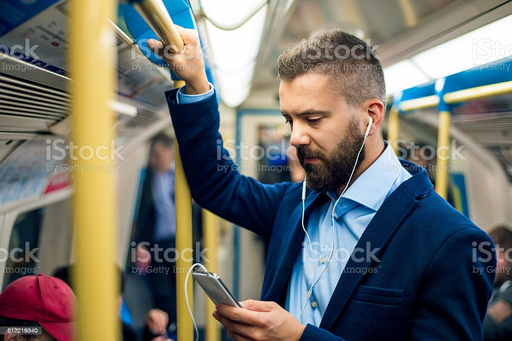 Serious businessman travelling to work. Standing inside undergro stock photo