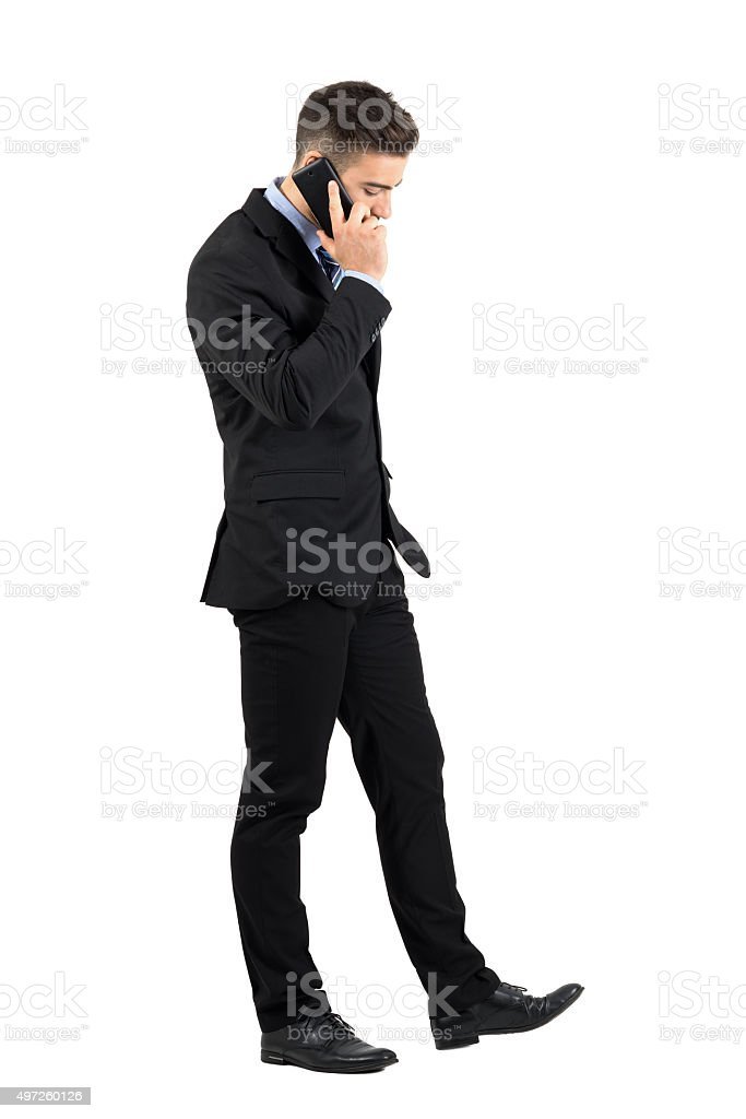 Serious businessman walking and talking on his cellphone side view stock photo