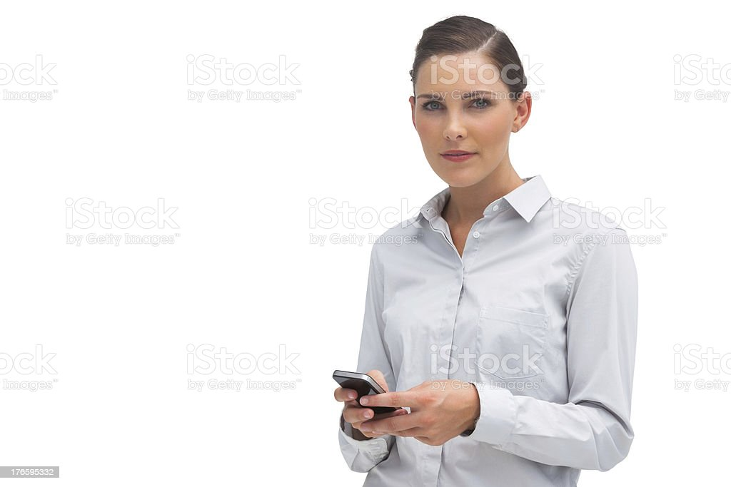 Serious businesswoman holding mobile phone royalty-free stock photo