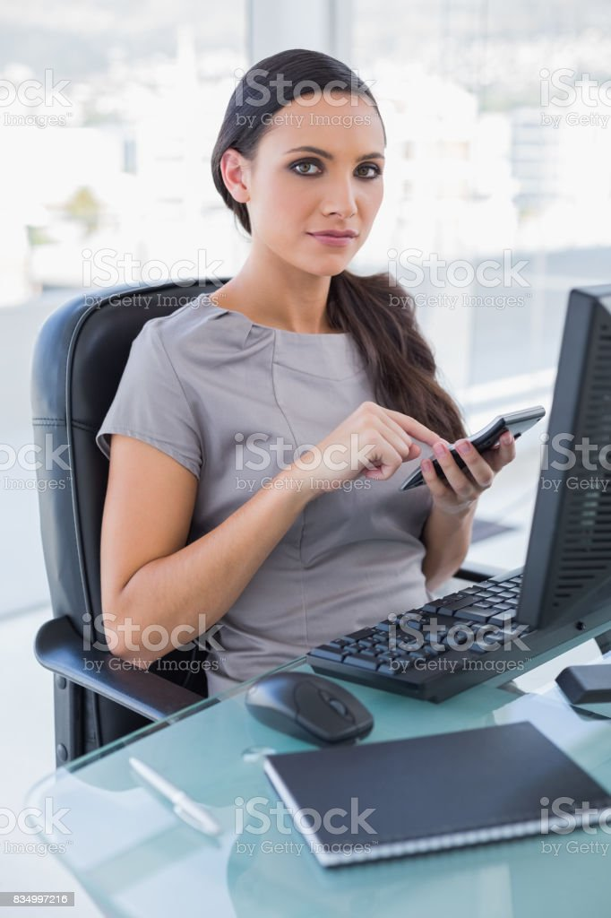 Serious businesswoman using calculator and looking stock photo