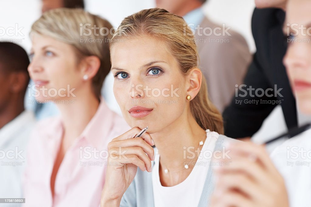 Serious businesswoman with colleagues during a seminar stock photo